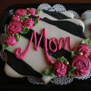 white fancy plaque cookie with black painted stripes and rosette clusters in Bubble Gum Pink with inscription to match