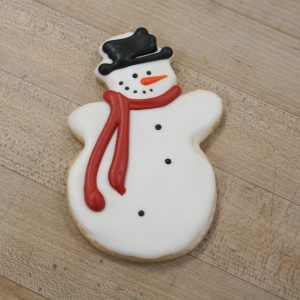 Snow man frosted cookie with red scarf, carrot nose and black eyes, buttons and mouth