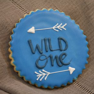 scalloped edge round cookie with royal blue icing and wild one written in navy with 2 white arrows